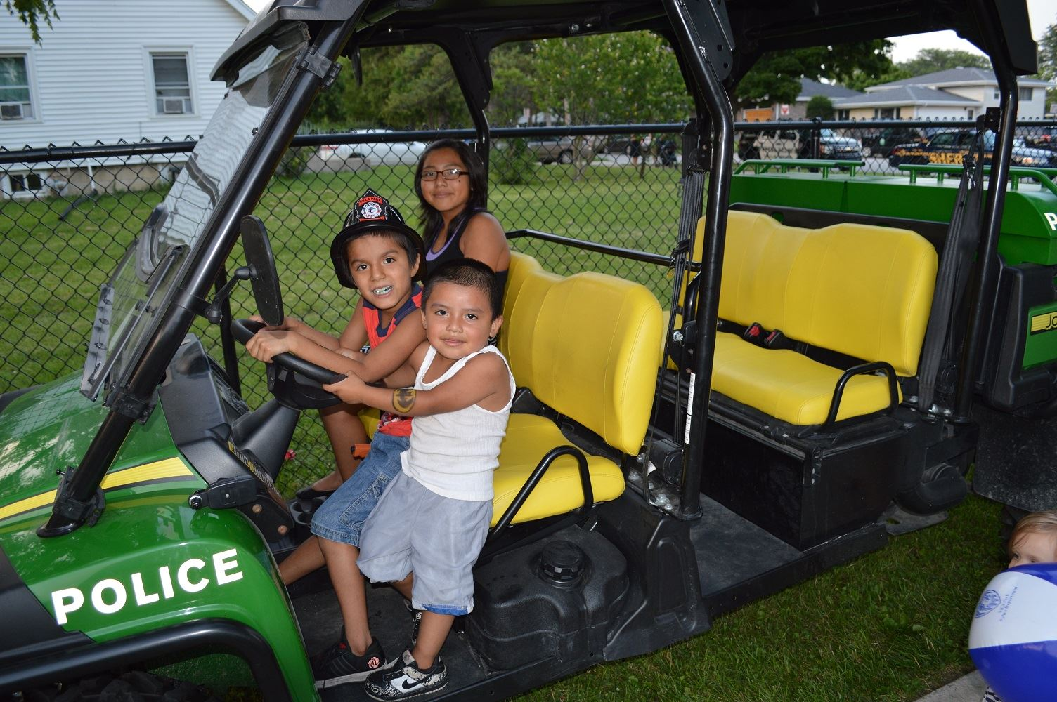 Three children check out the front seat of the Villa Park Police Gator vehicle during a National Night Out event at the Iowa Community Center, Aug. 2.